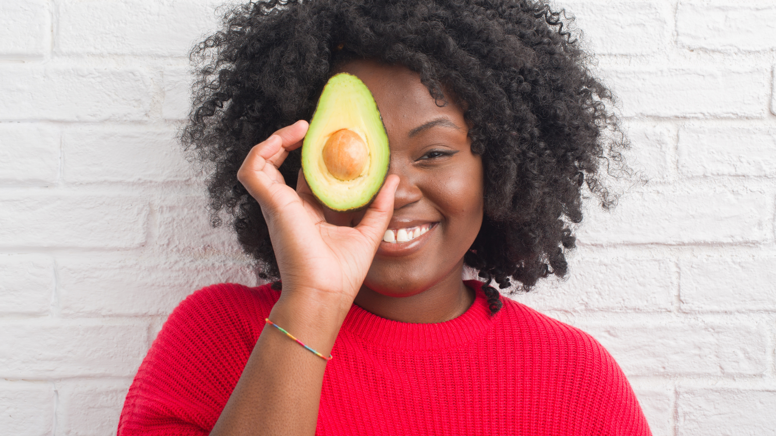 Young african american woman over white brick wall eating heart-healthy avocado