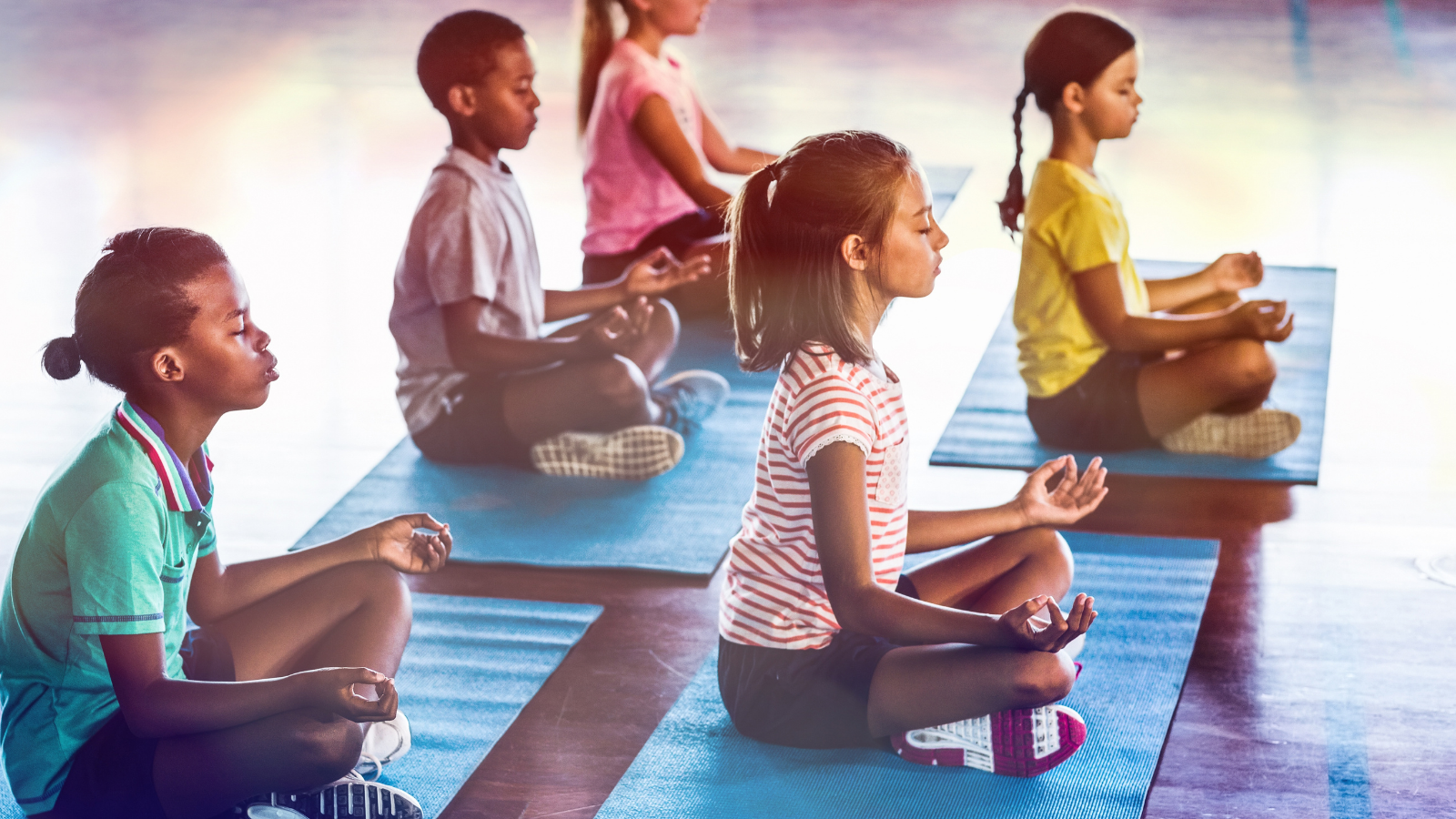 Kids in yoga class experiencing the benefits of yoga on their general ease and calm