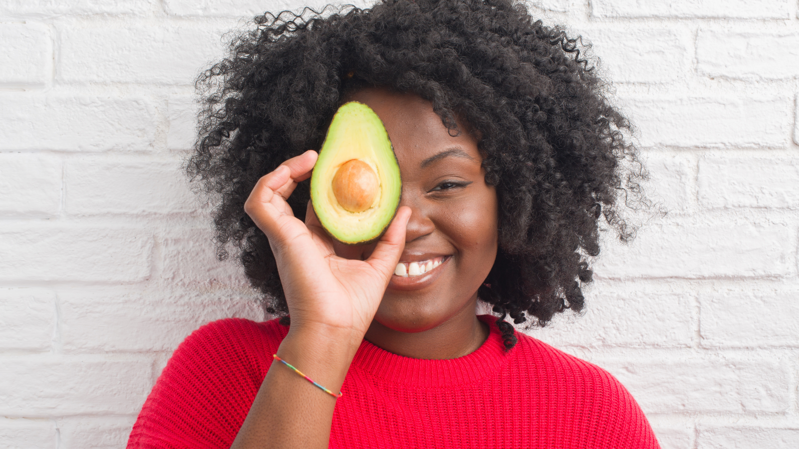 Young woman by white brick wall eating avocado with a happy face standing and smiling with a confident smile
