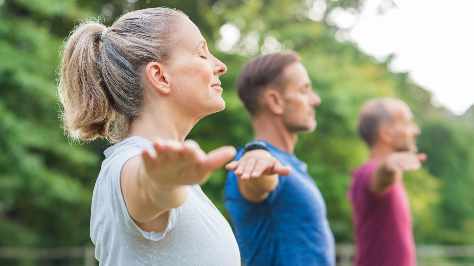 Group of senior people with closed eyes stretching arms at park