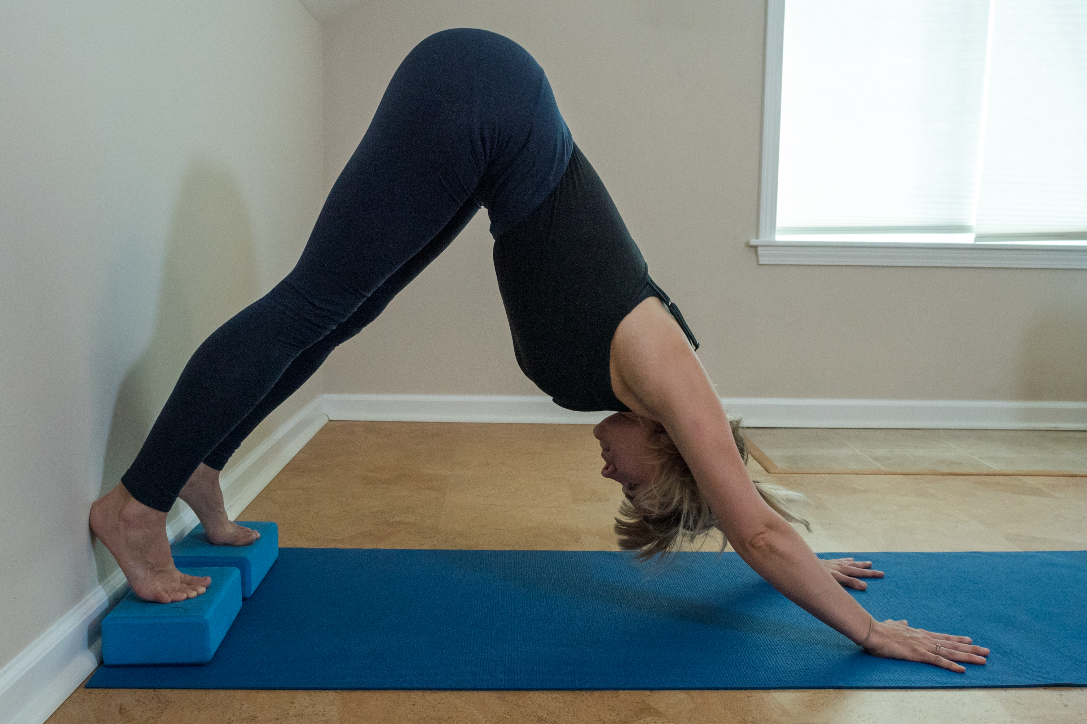 woman preparing for handstand with downward dog with heels elevated