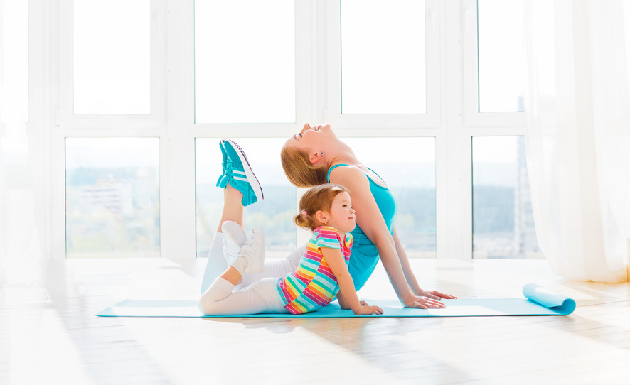Child and parent practicing yoga together