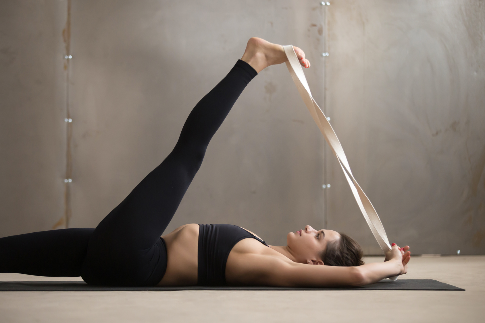 woman practicing yoga supta padangustasana, reclining hand to big toe pose with prop strap motidification