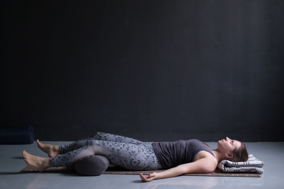 Woman practicing supported savasana
