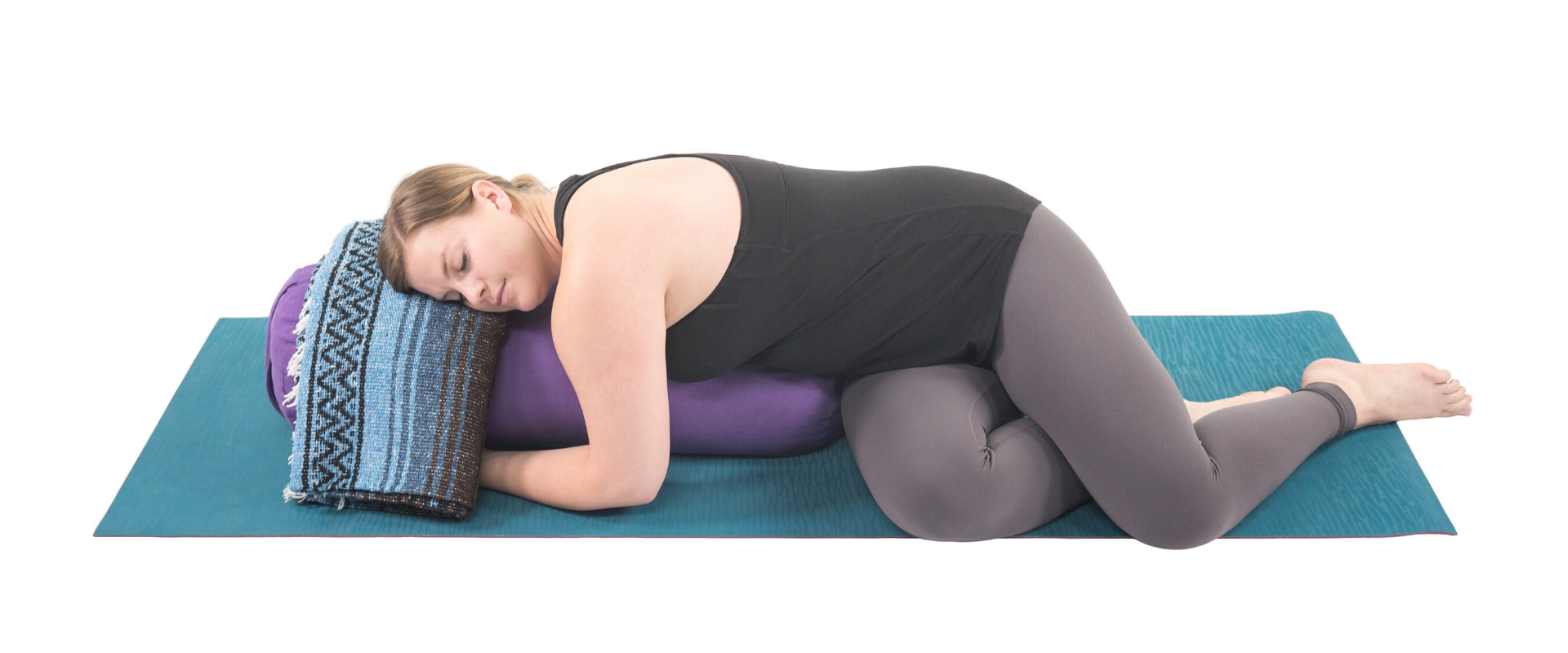 Woman practicing restorative yoga twist on a bolster.