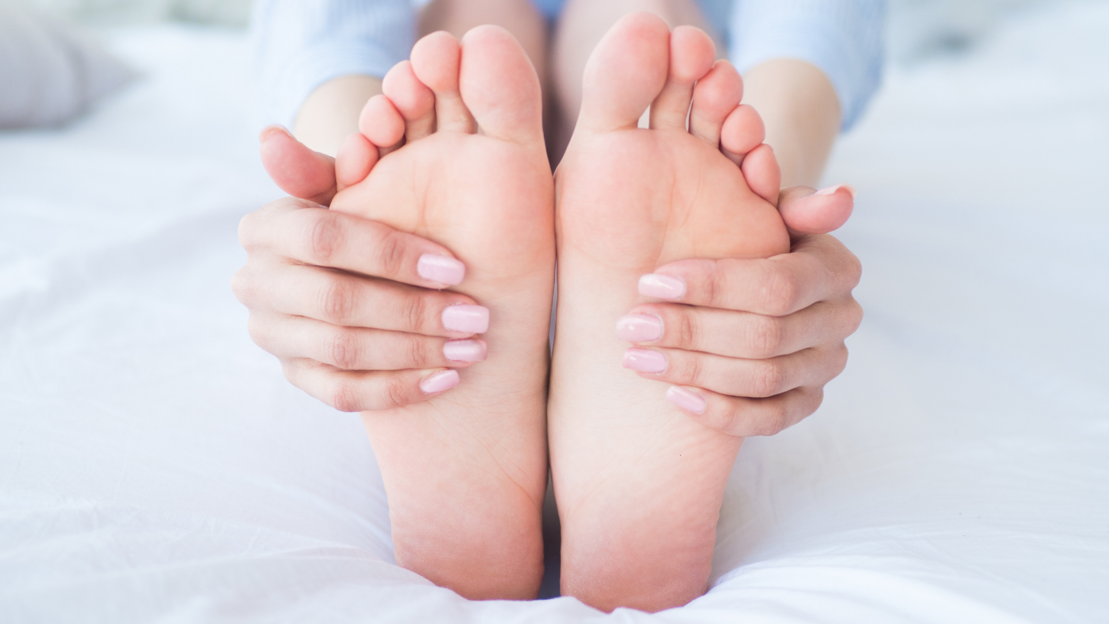 Young woman on bed massaging her feet for better health and wellbeing