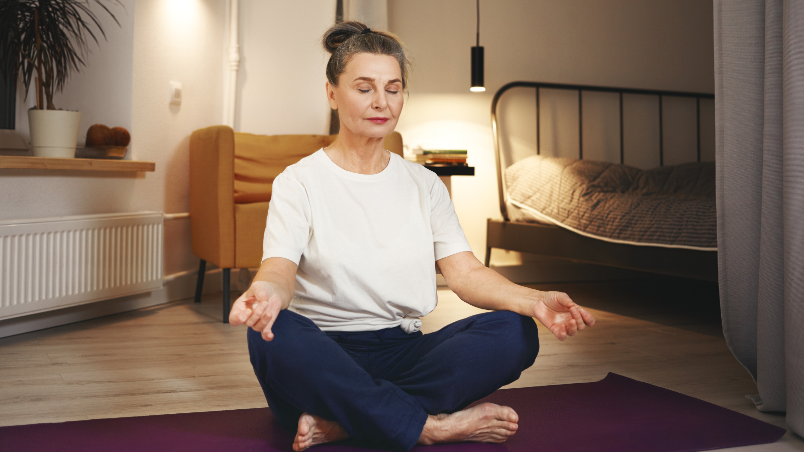 Senior woman sitting barefooted on floor at home, keeping legs crossed on mat, doing meditation after yoga practice, having calm peaceful facial expression
