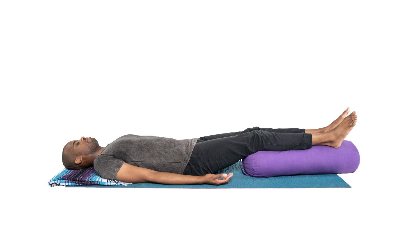 Yoga student practicing Simple Supported Savasana pose to put the body in the healing rest and digest state