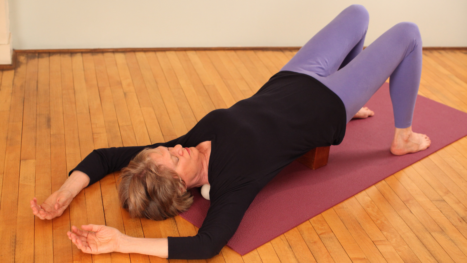 Back and shoulder routine using exercise balls under your trapezius and a block to support your lower back to release tension