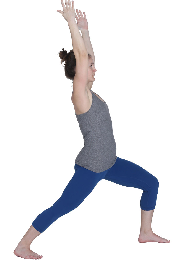 A woman in Warrior 1 yoga pose (Virabhadrasana I)