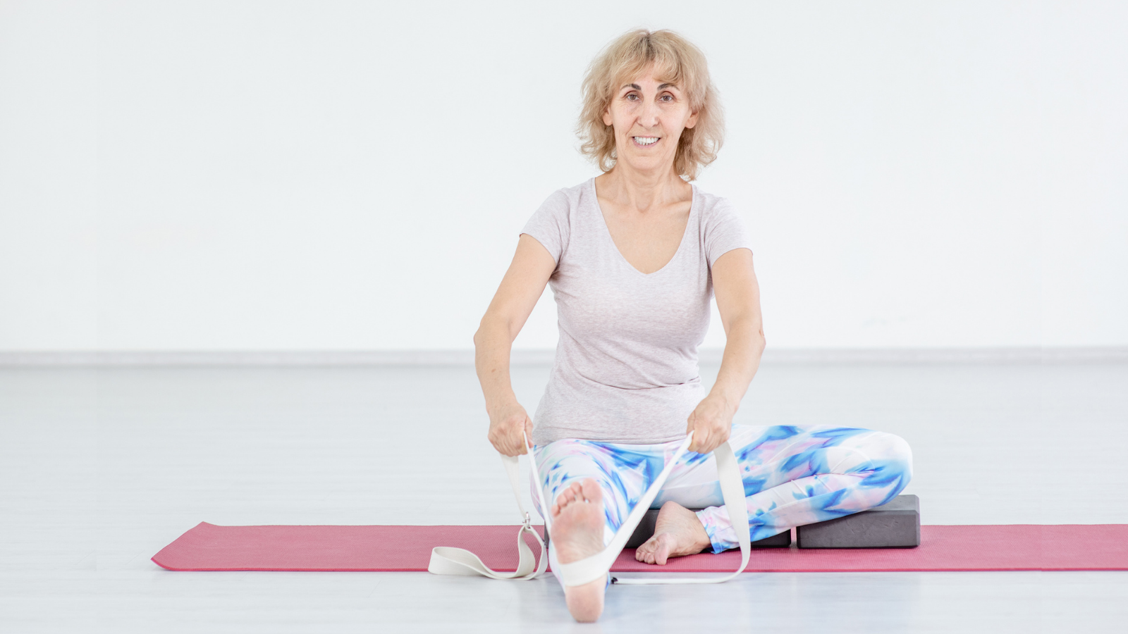 The benefits of using a strap to support the spine in Head-to-Knee yoga pose (Janu Sirsasana)