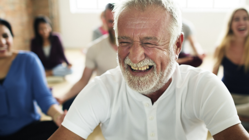 Happy older man smiling as he practices yoga