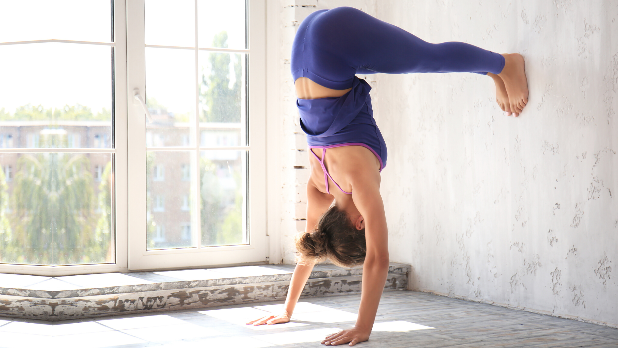 woman practicing handstand with wall.