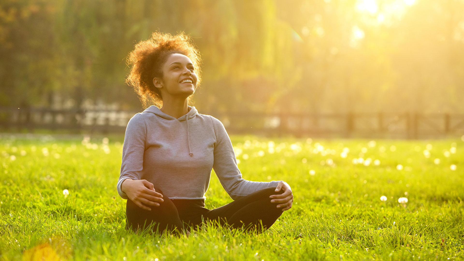 Young woman happily sitting outside in beautiful field.