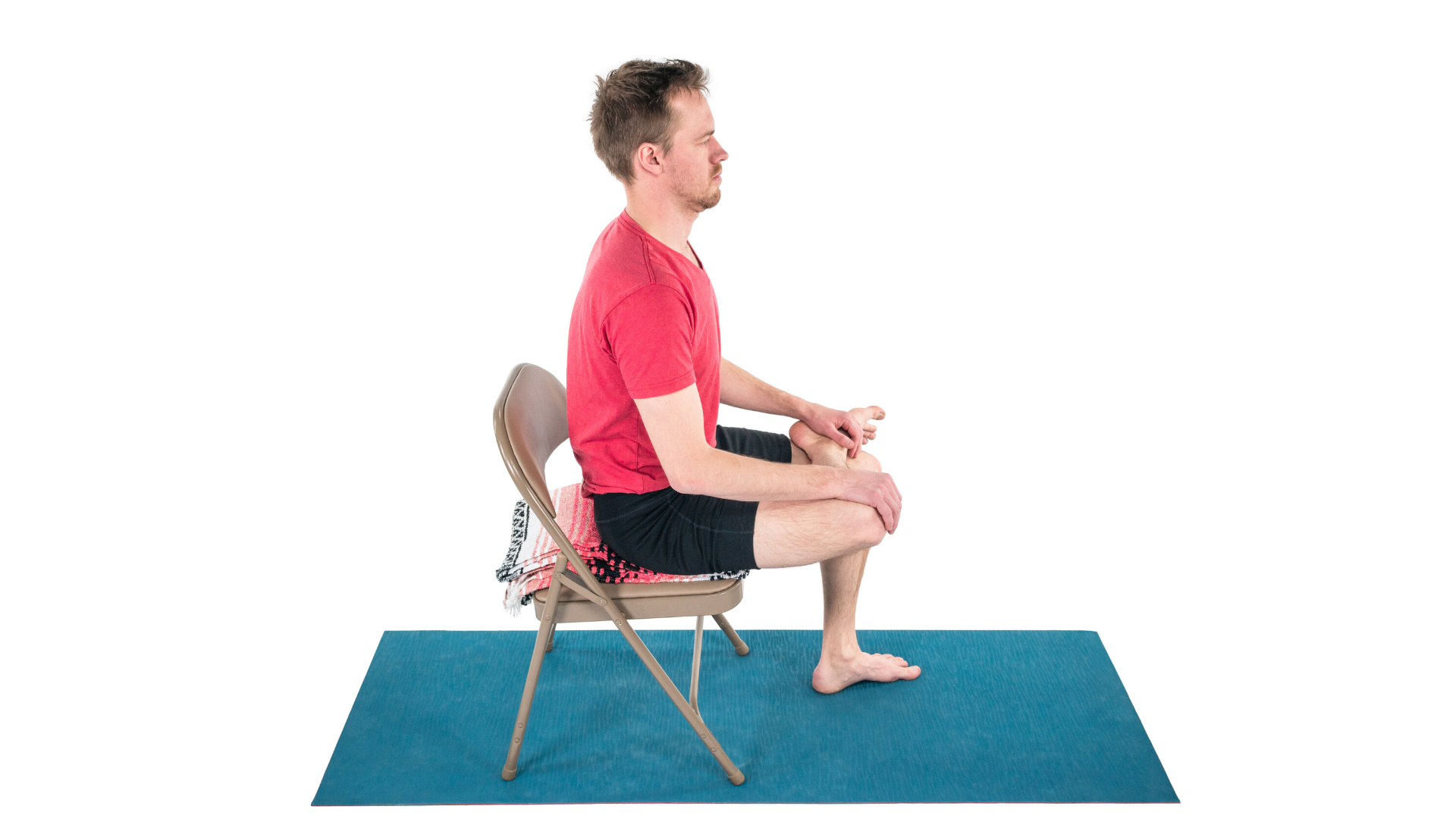 Man practicing yoga seated figure four stretch.
