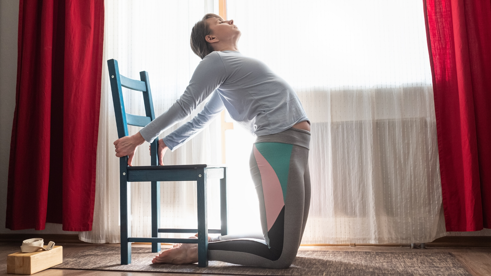 female yoga student practicing gentle yoga with a chair at home.