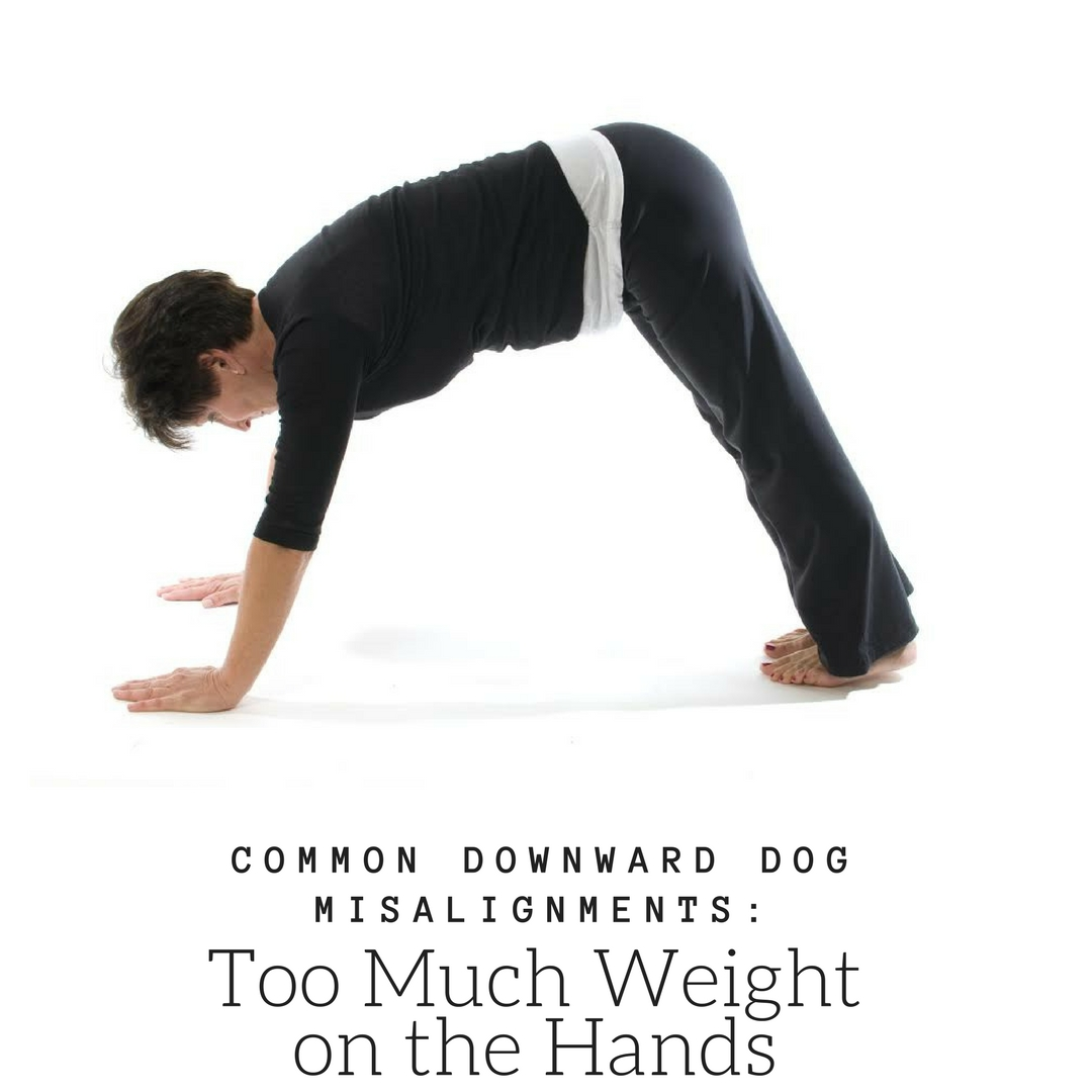 A woman in downward facing dog, (Adho Mukha Svanasana) in a common misalignment: too much weight on the hands
