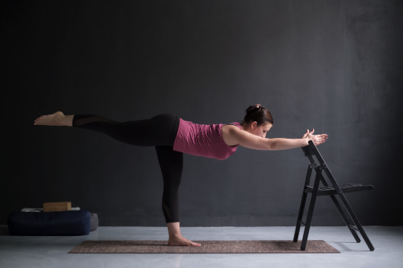 Woman practicing iyengar yoga warrior 3 with a chair