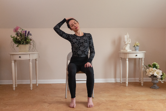Woman seated in a chair stretching her neck yoga