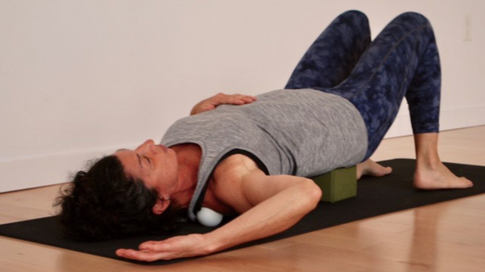 A yoga student in class practicing myofascial release with the use of a yoga block and props