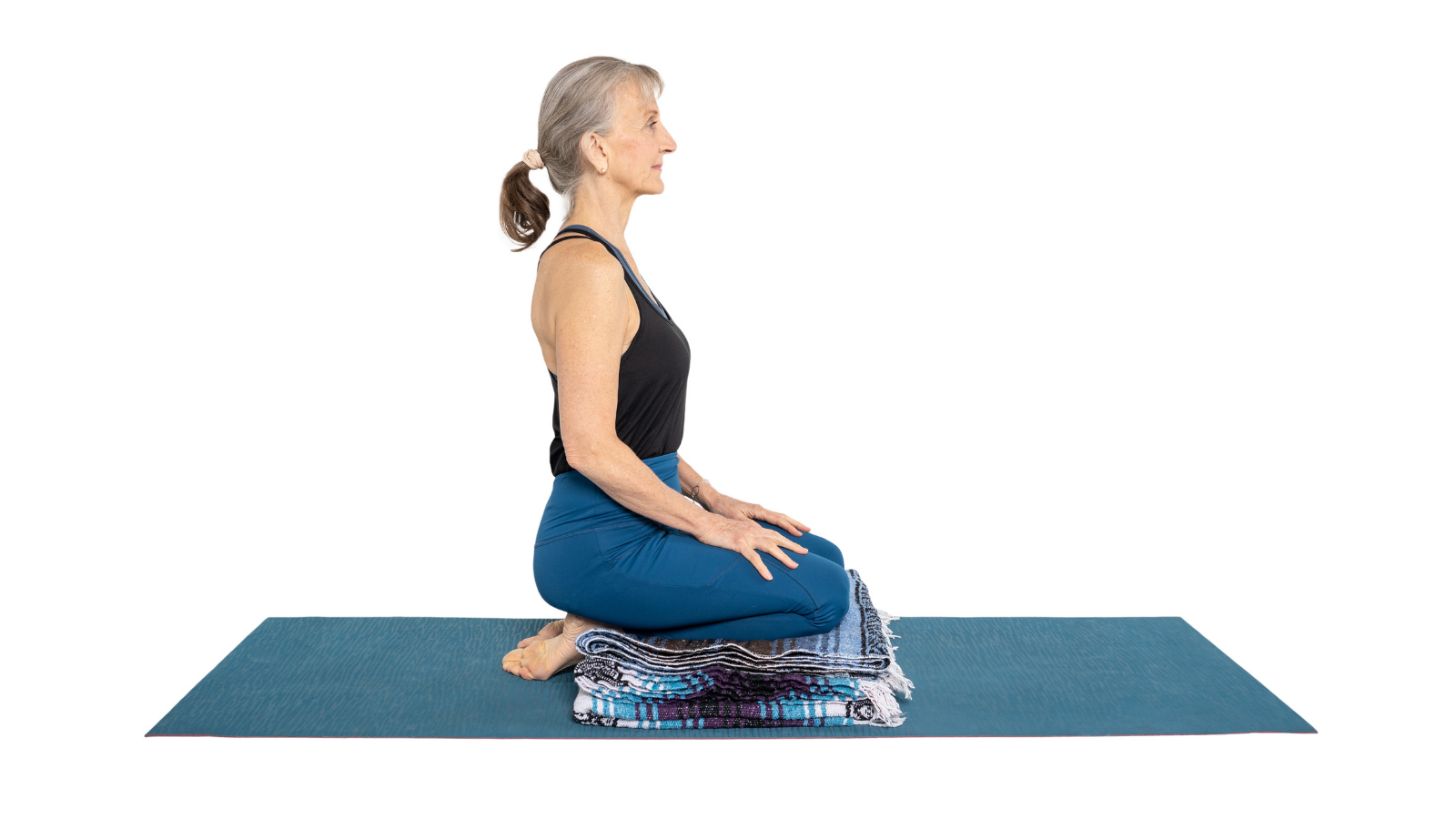 Woman sitting in Hero's Pose or Virasana to work on facial exercises to help with TMJ pain