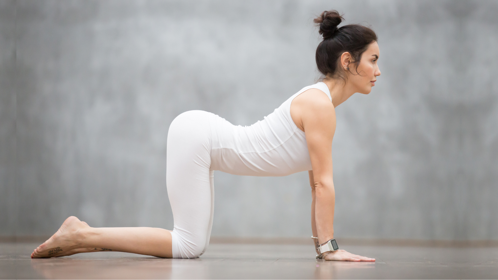 Beautiful young woman with tattoo doing yoga's Cat/Cow Pose