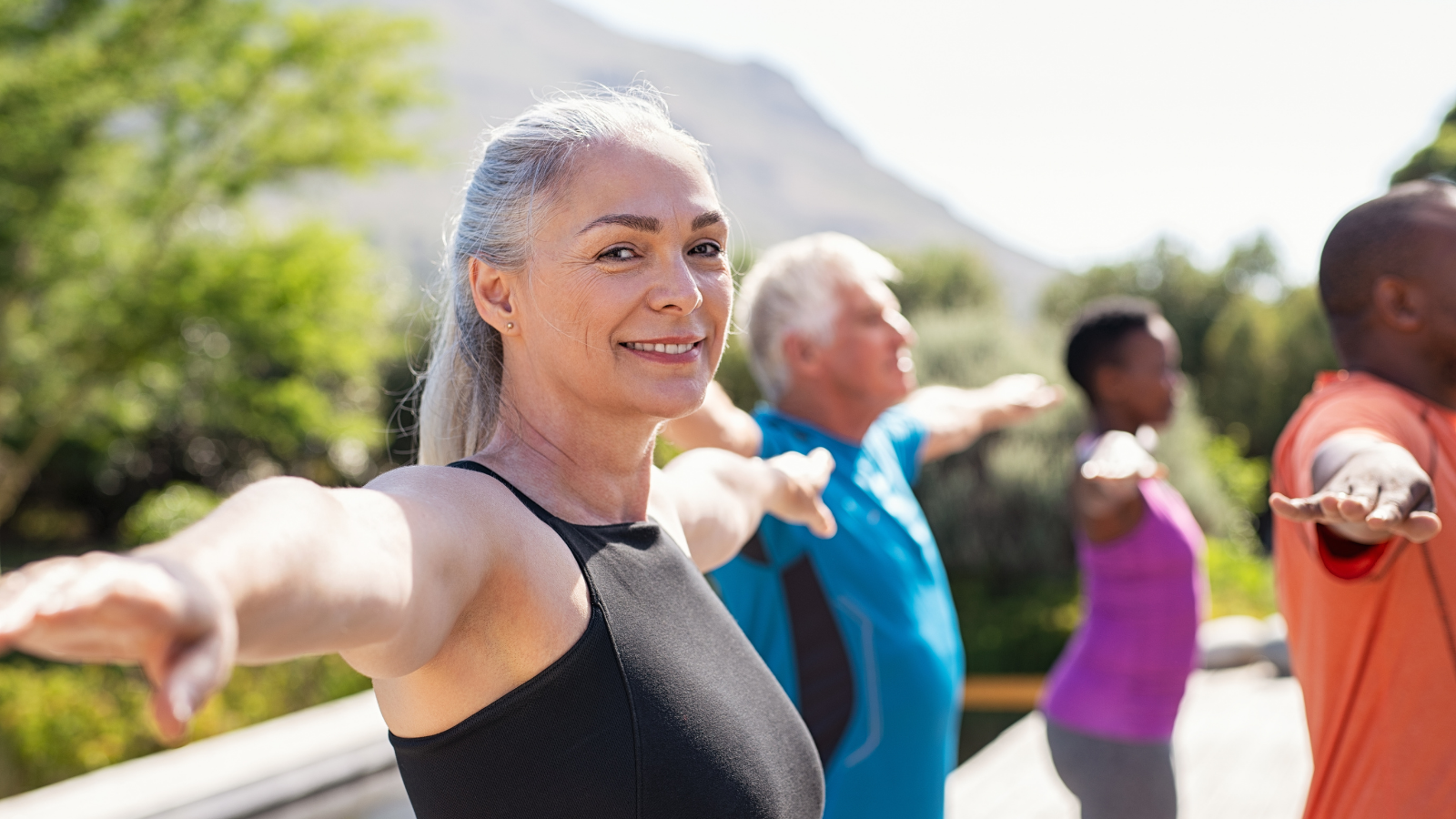 Happy senior woman practicing yoga outdoor with her fitness class