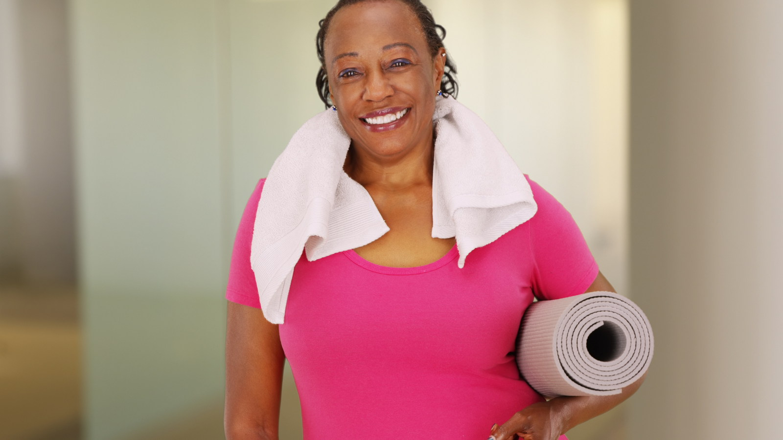 African American woman with genuine smile poses for a portrait after her workout