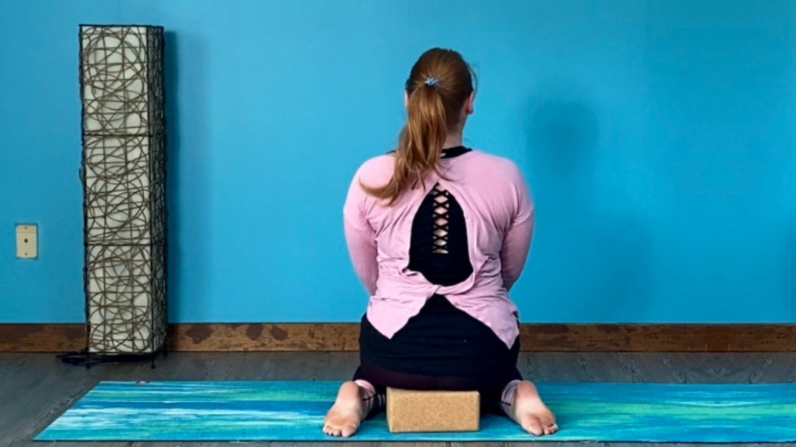 In a yoga class, a student practices Hero Pose (Sanskrit name) to experience the benefits of healthy knees, hips, and ankles