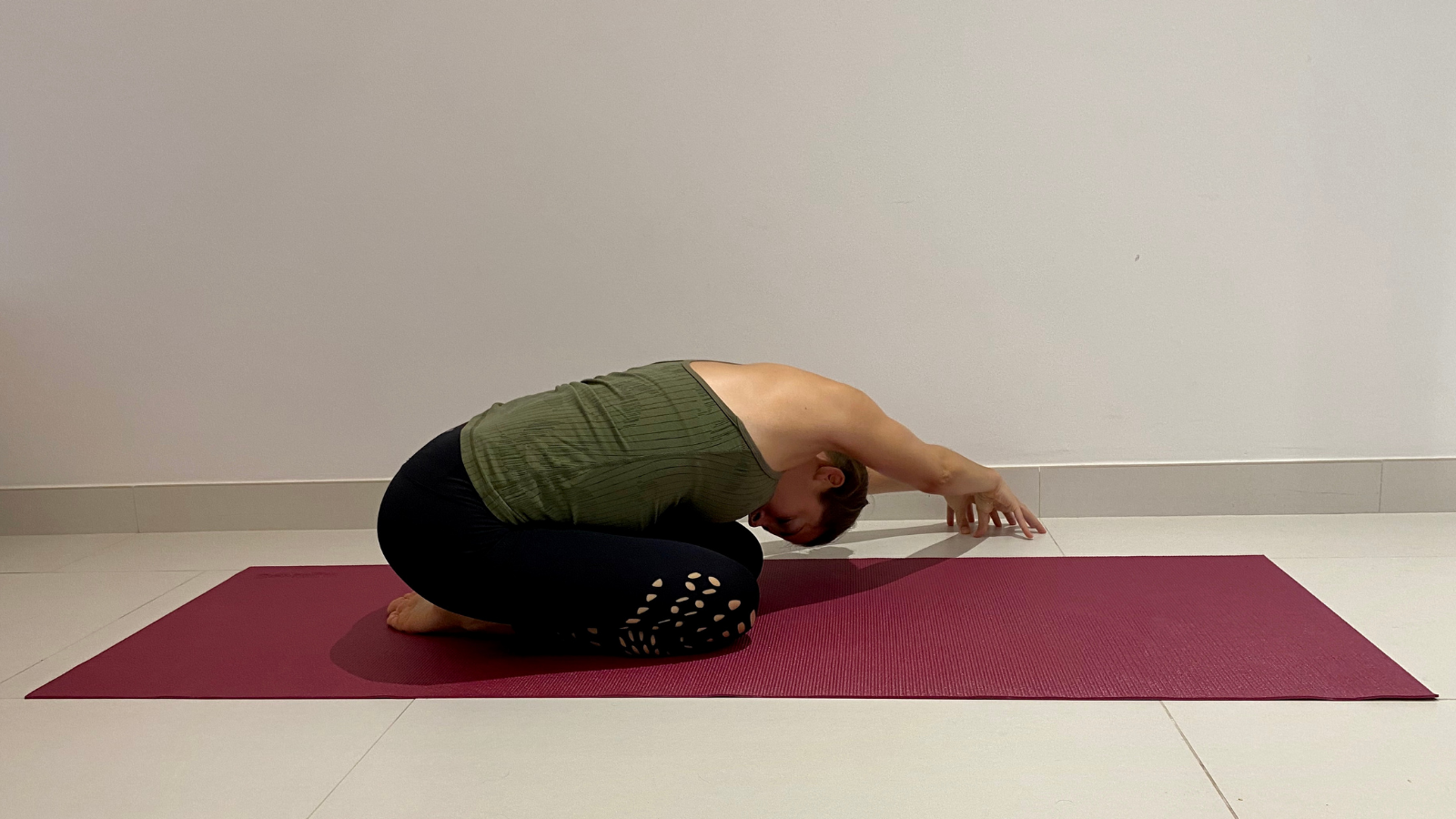 The benefits of practicing Side Reaching Child's Pose (Balasana) to stretch muscles of the back body and ease back pain