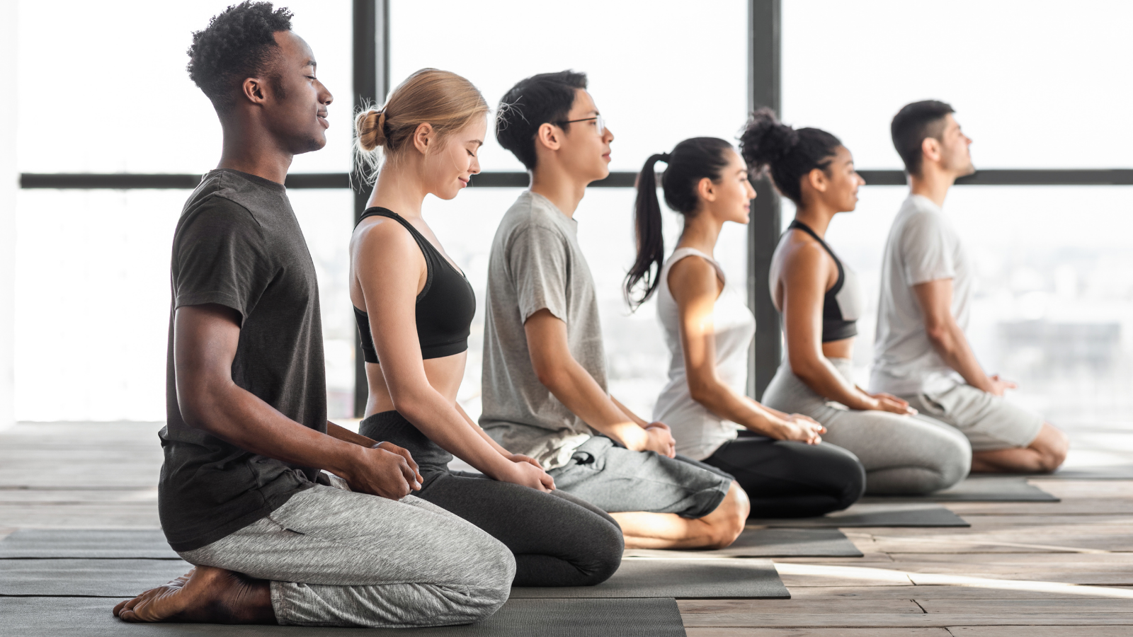 """Yoga students at the end of class experiencing the positive effects of saying and meaning the word """"namaste"""""""