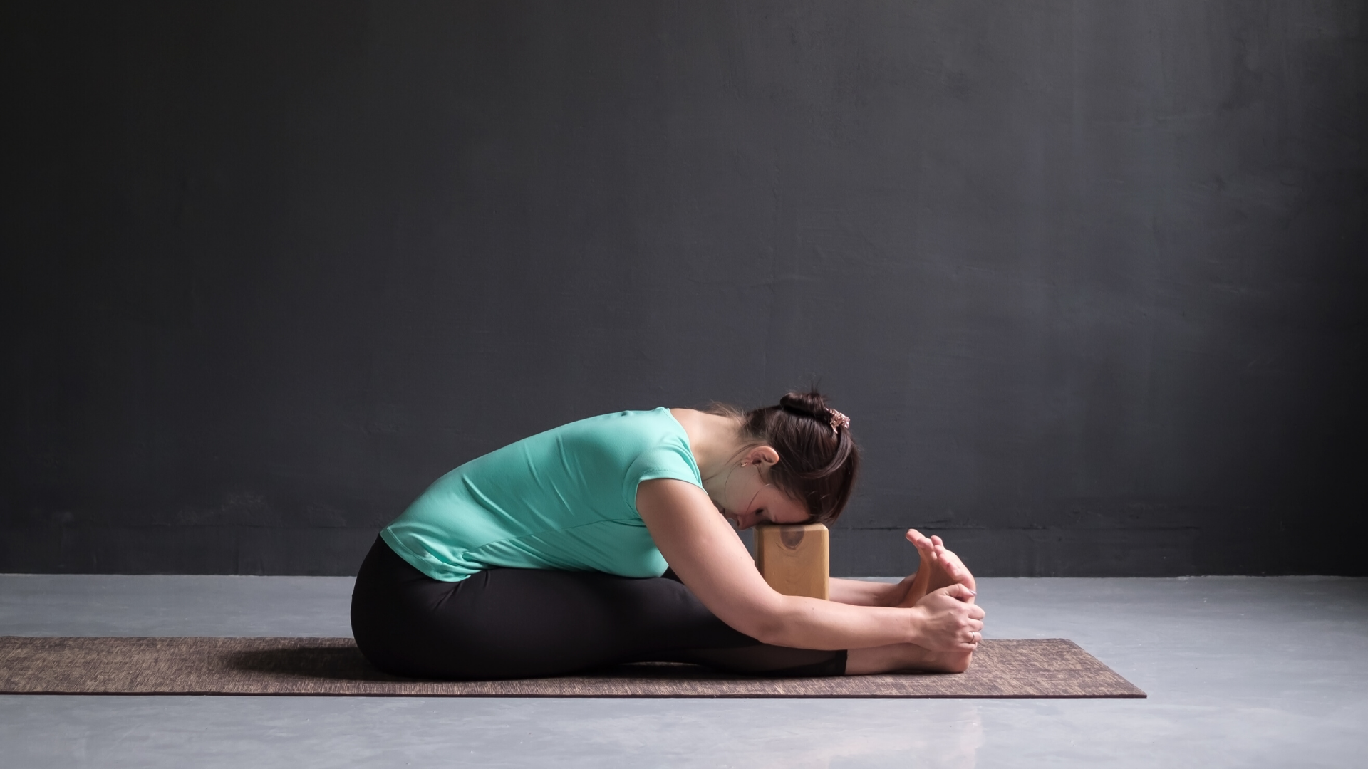 yoga_instructor_demonstrating_how_to_practice_seated_forward_bend_in_yoga_at_home