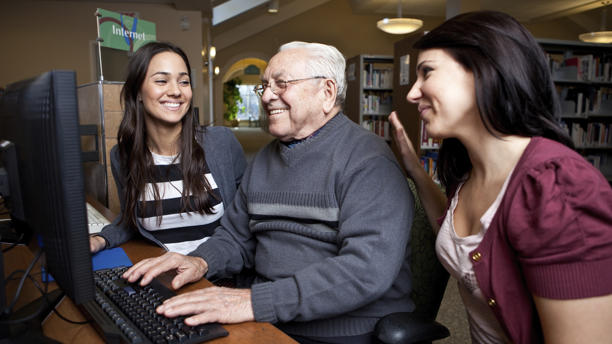 Two girls helping elderly man on the computer.