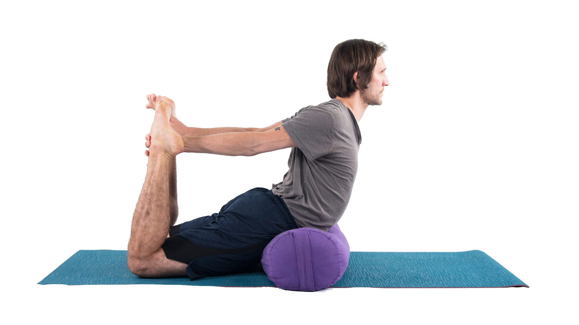 Man practicing dhanurasana bow pose with props.