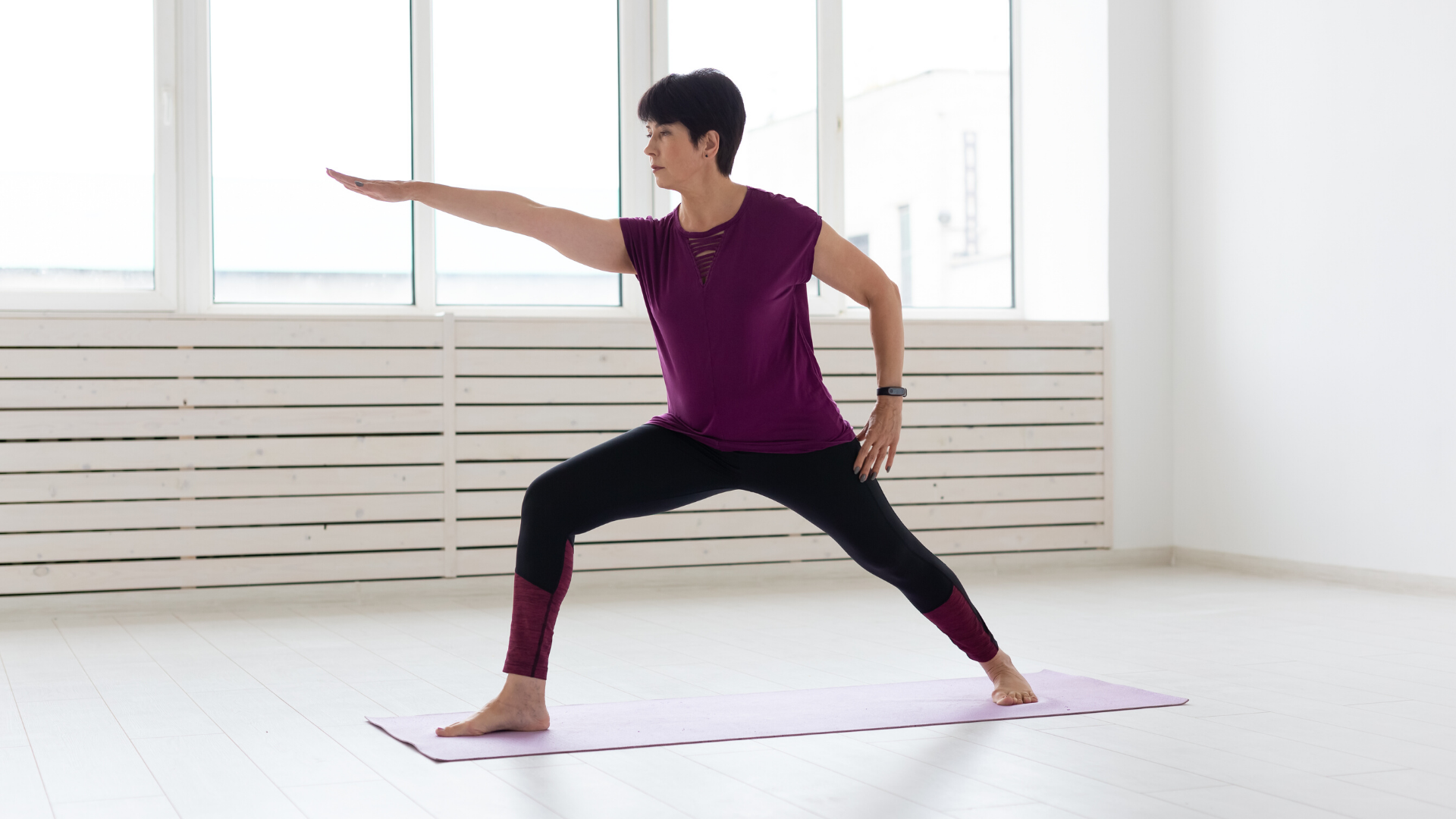 Woman practicing yoga warrior II pose.
