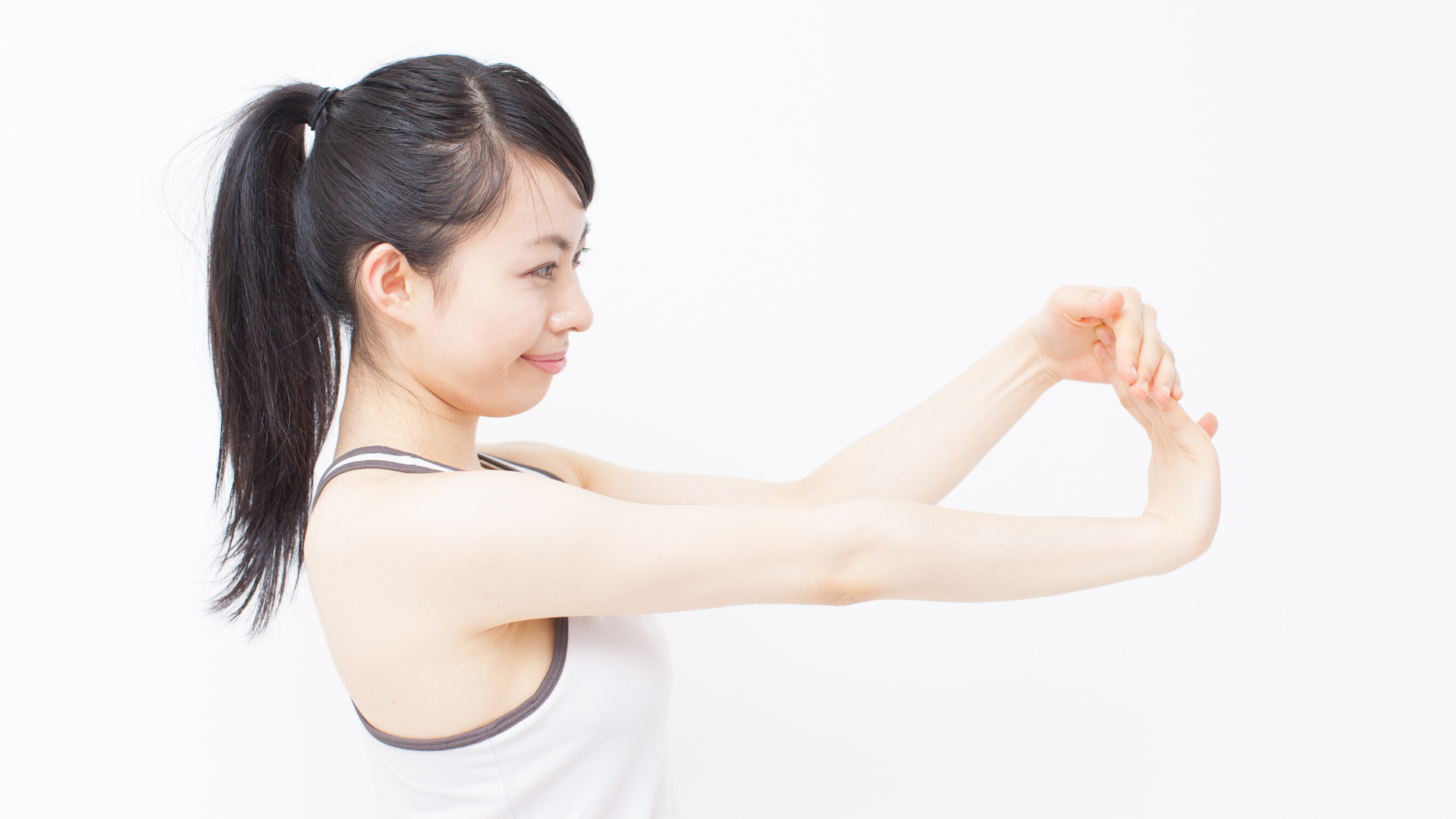 Woman practicing yoga wrist stretch.