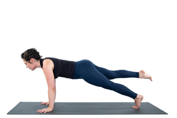 Woman practicing plank pose with one leg off the ground