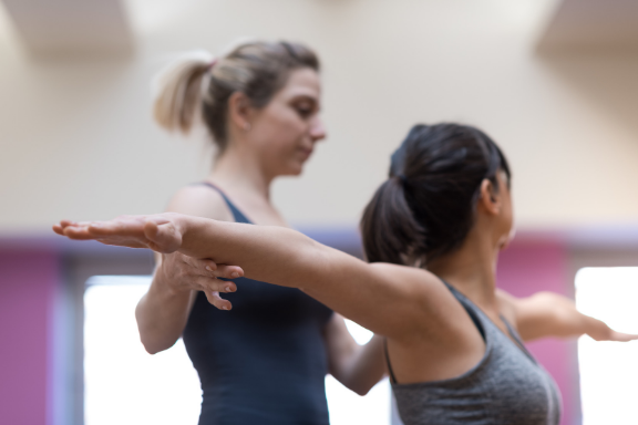 Woman practicing warrior 2 receiving individual instruction from a yoga therapist