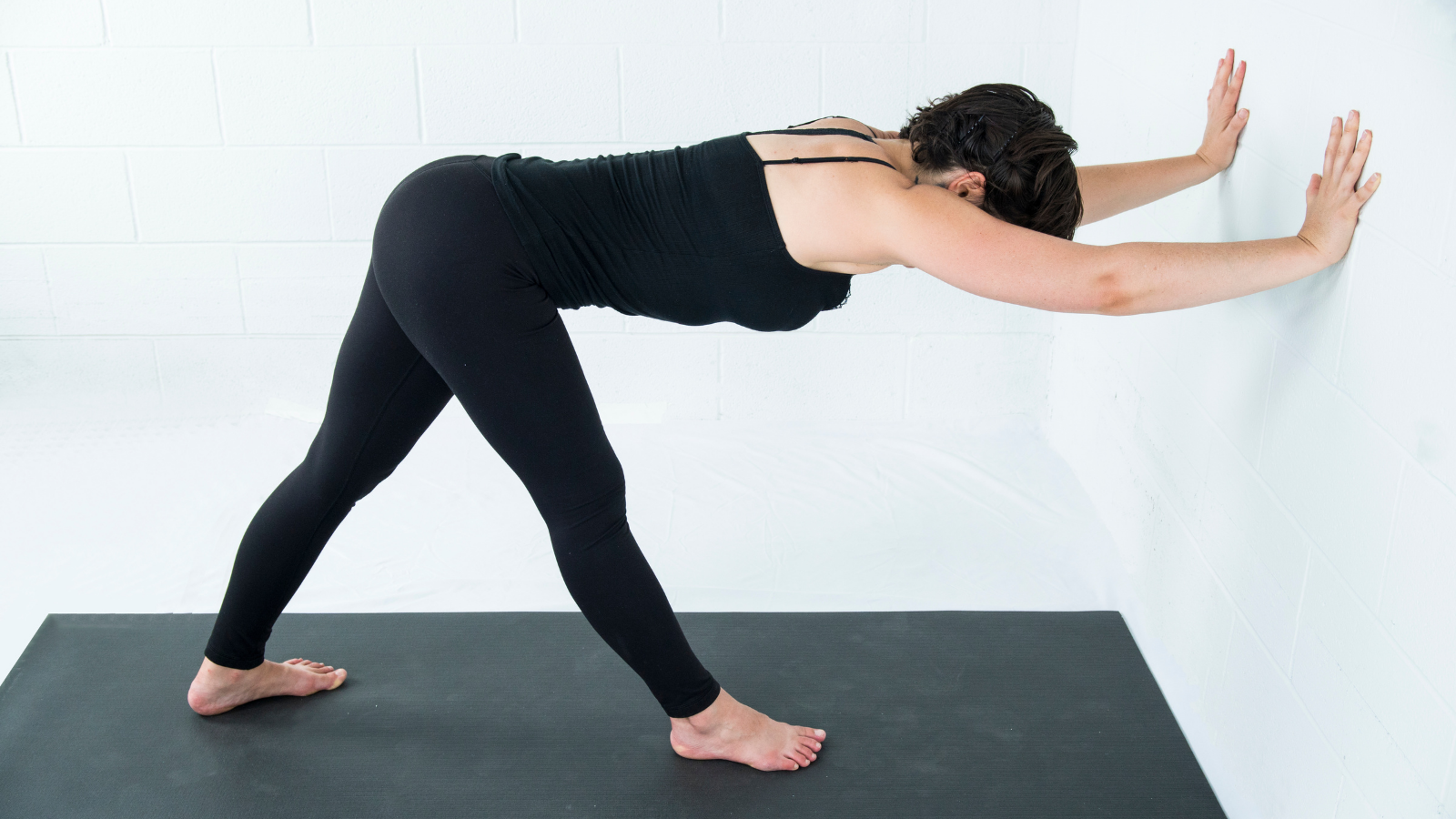 Yoga student practicing Pyramid Pose (Parsvottanasana) at the wall to adapt the pose to her body