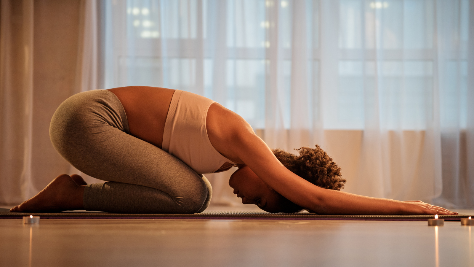 peaceful young woman stretching while doing yoga exercise as a great preparation for a good night's sleep