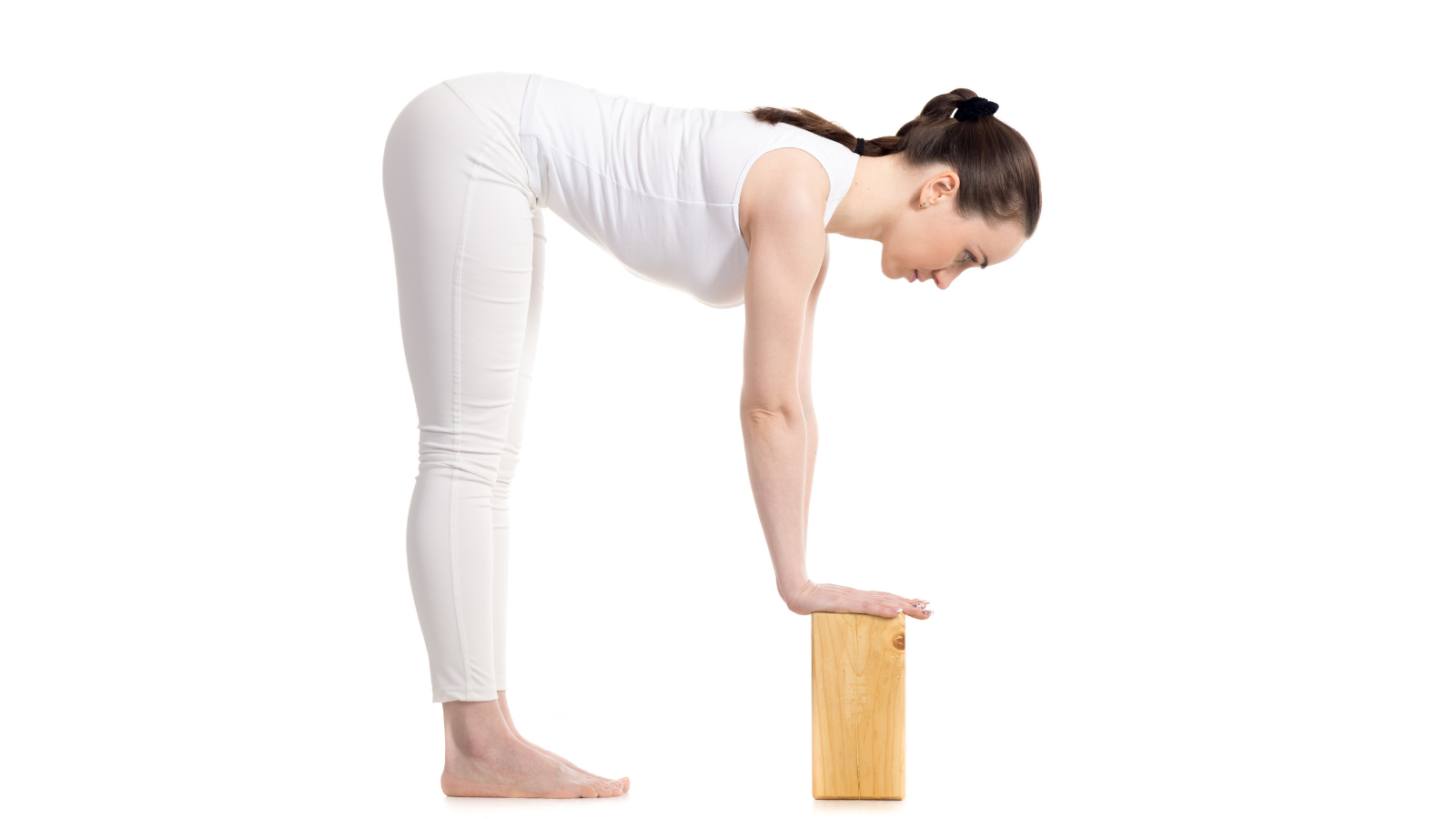 Yoga practitioner experiencing the benefits of safely practicing a modified version of Standing Forward Bend Pose (Sanskrit name: Uttanasana)