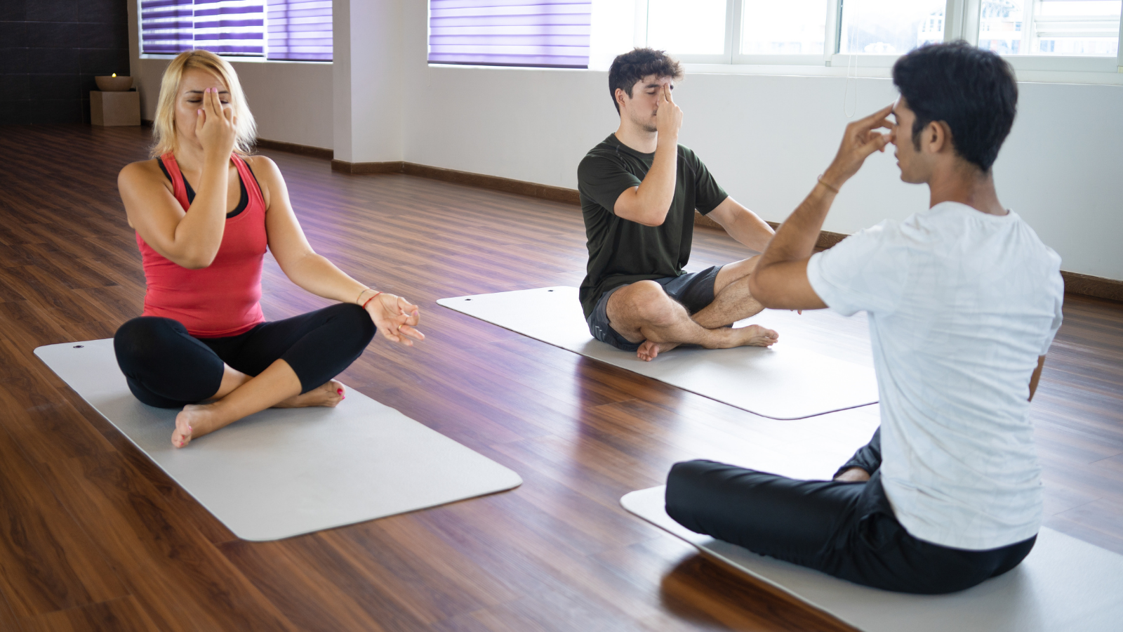 Students practicing breathing technique with instructor at yoga class which may help COVID patients improve breathing rates