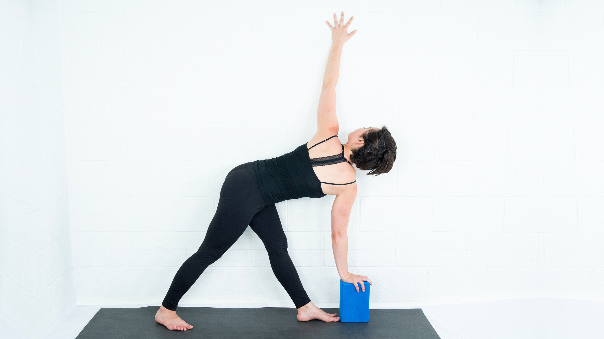 Woman practicing revolved triangle variation at the wall.