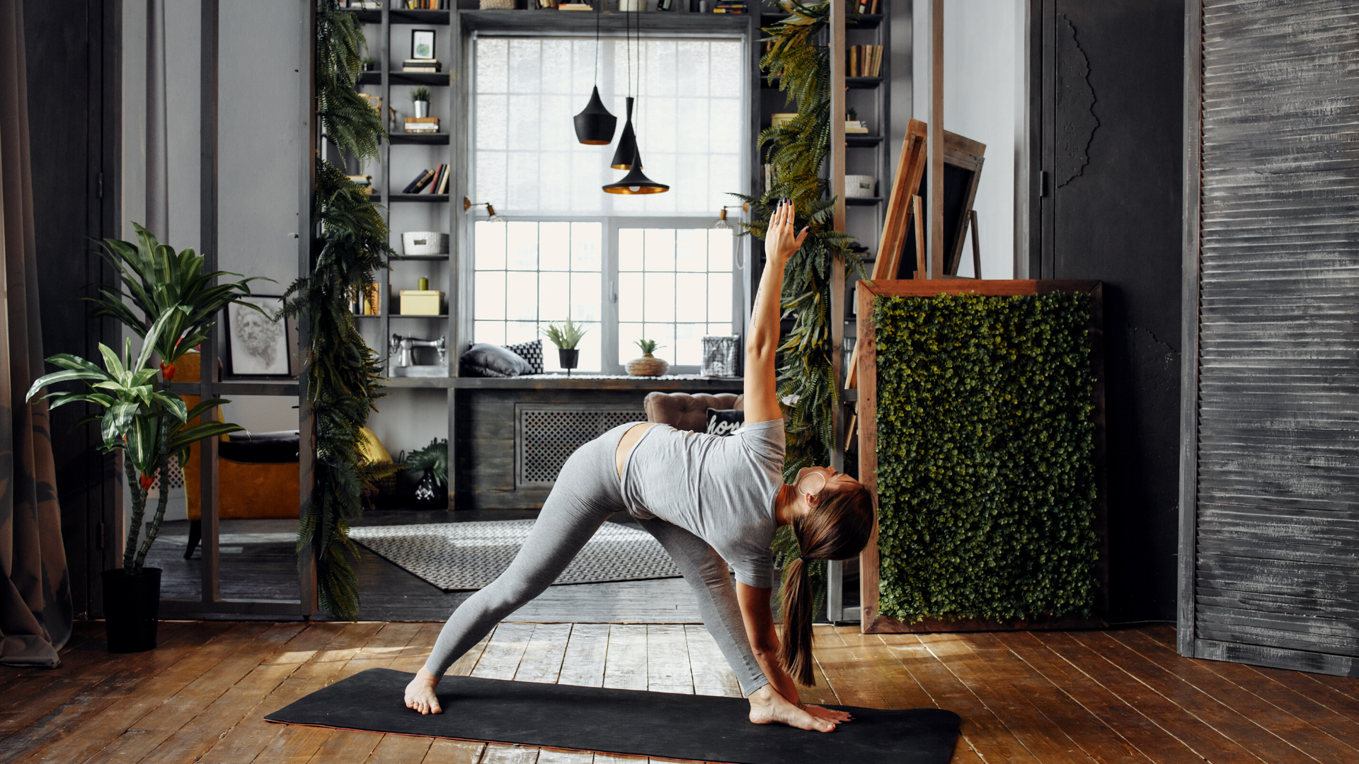 Woman practicing yoga revolved triangle at home.