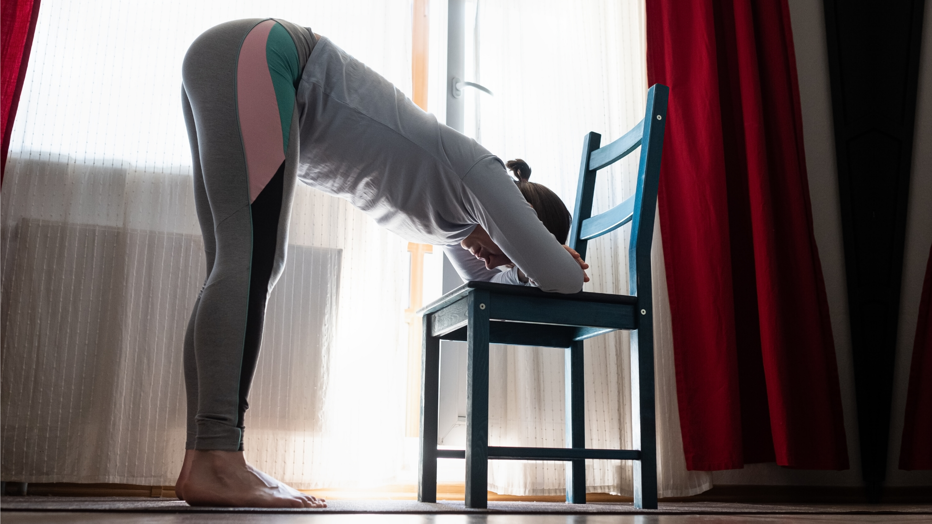 Woman practicing yoga forward bend (uttanasana) with chair modification.
