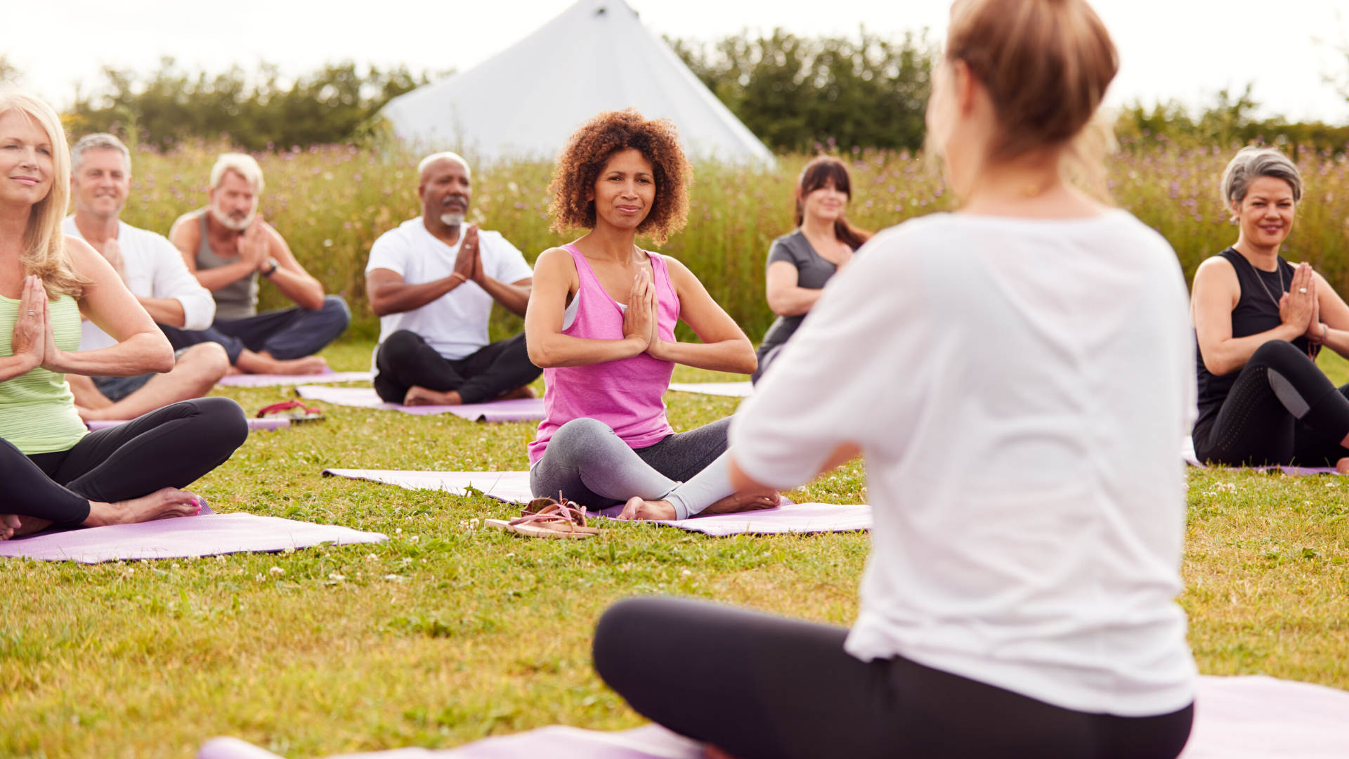 group of middle-aged yoga students practicing yoga outdoors.