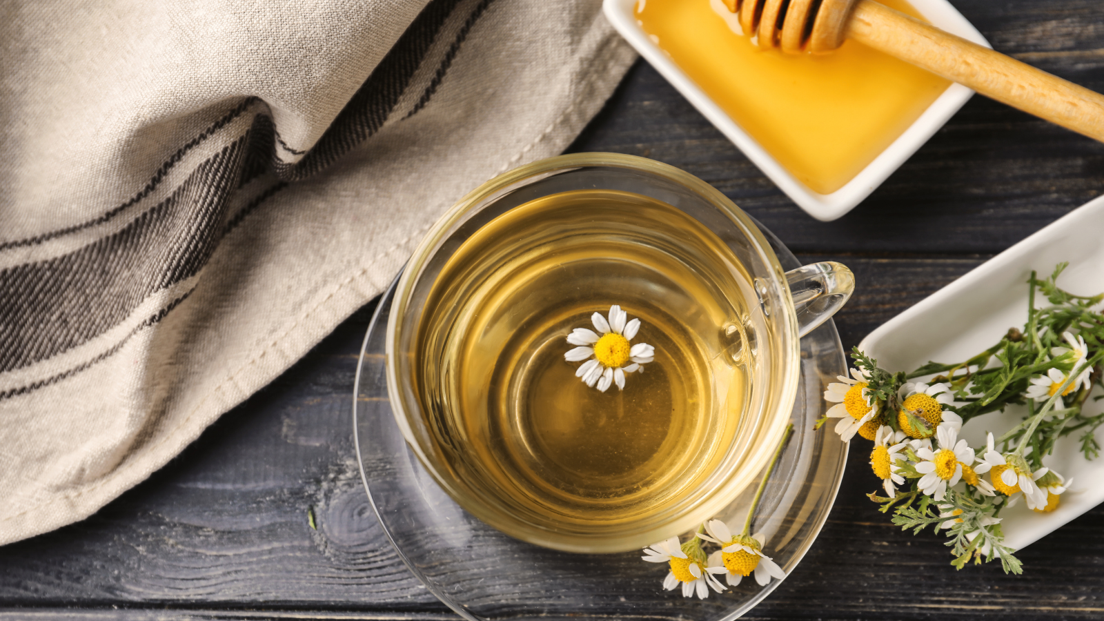 Cup of delicious camomile tea and honey on wooden table to have better sleep