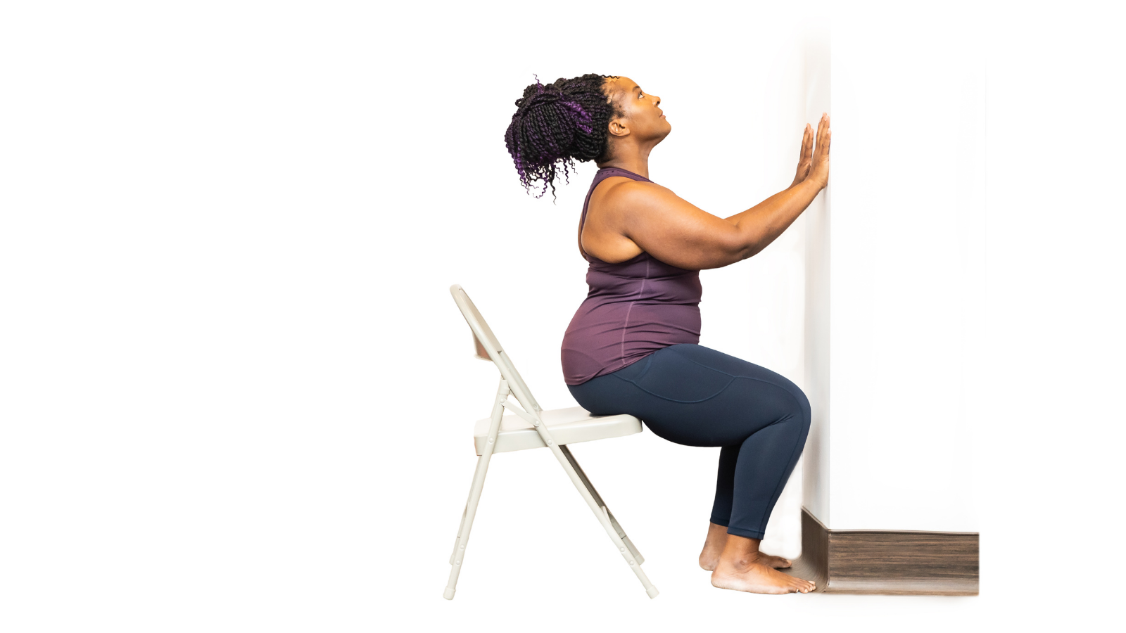 Yoga Student practicing Cobra Pose (Bhujangasana) with chair and at the wall to assist her
