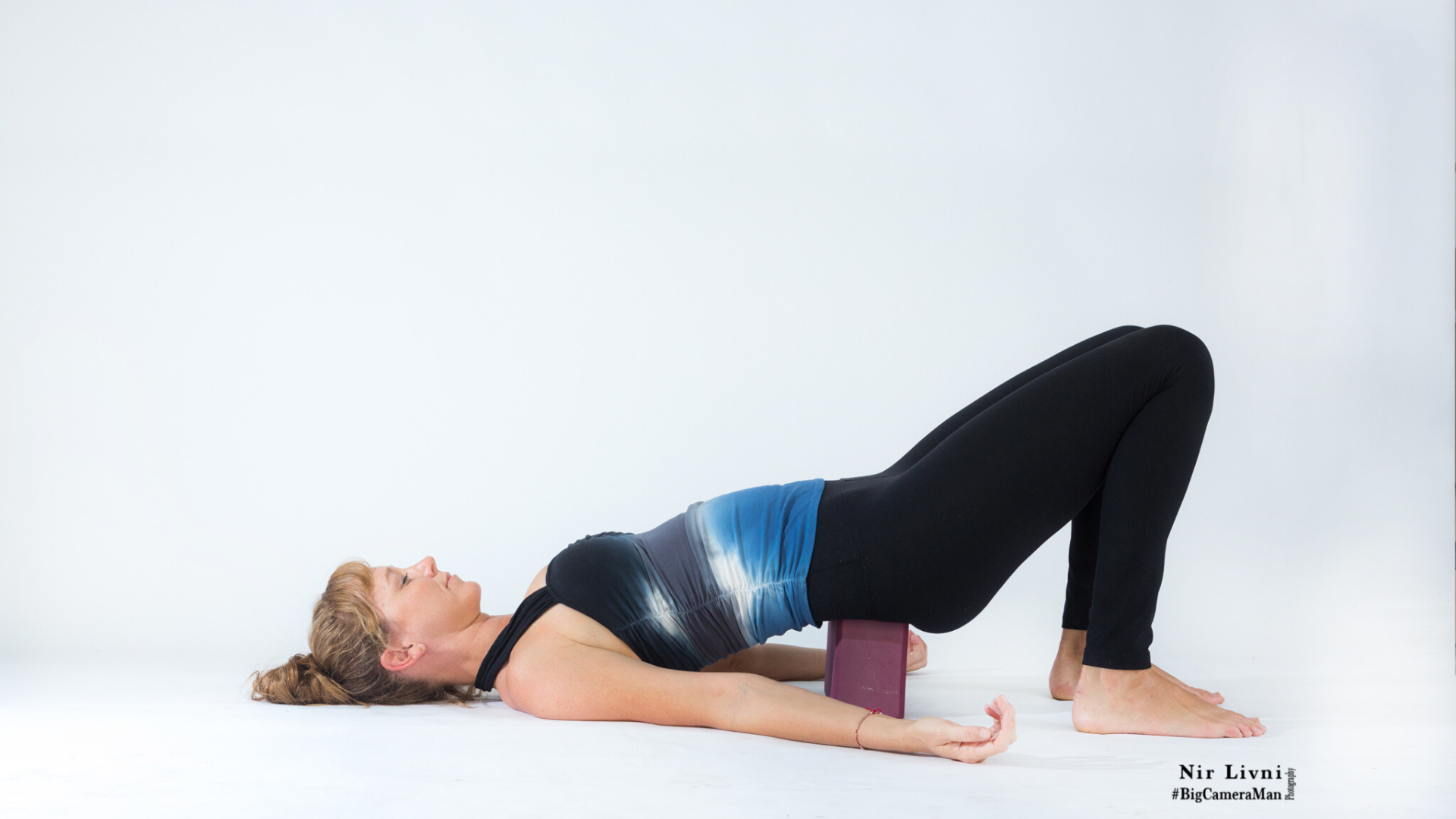 Woman practicing supported bridge pose.