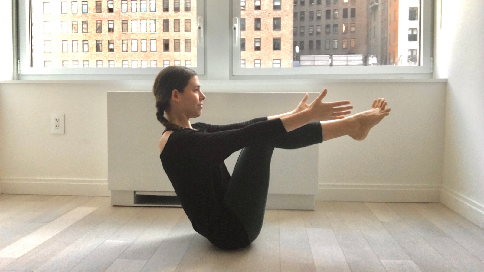 Yoga student practicing Boat Pose (Navasana) to build core and leg strength and establish stability for other postures